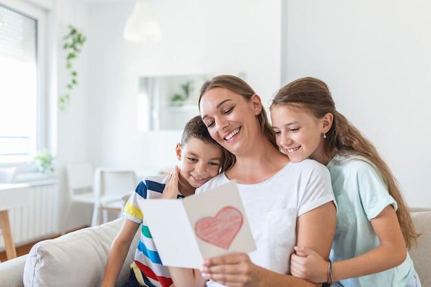 Vrolijke jonge moeder en kleine kinderen zittend op de bank en omarmen tijdens het lezen van wensen en felicitaties met vakantie in gepresenteerde ansichtkaart thuis