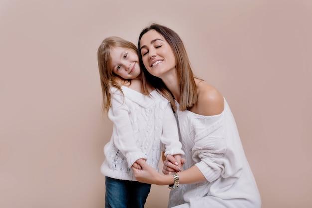 Vrolijke jonge moeder kijkt naar de camera, fluit en knuffelt een dochter