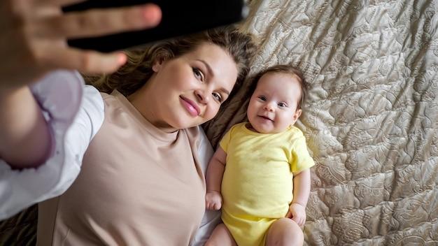 Vrolijke jonge moeder met krullend haar maakt foto van dochter
