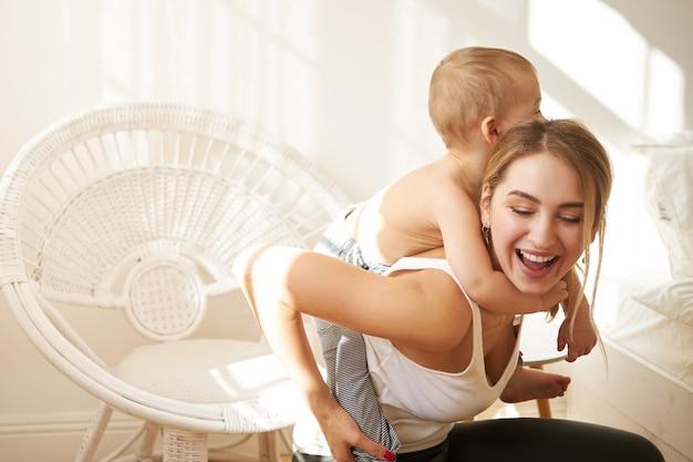 Vrolijke jonge moeder plezier binnenshuis piggy back rit geven aan haar schattige peuter zoon. aantrekkelijke moeder tijd doorbrengen in de kinderkamer, spelen met kind tijdens sociale afstand vanwege quarantaine