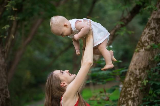 Vrolijke jonge moeder voedt de baby in haar armen. gelukkig moederschap en jeugd.