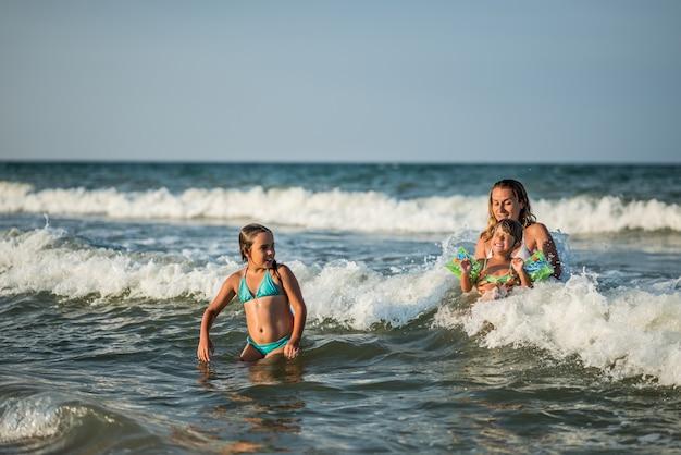 Vrolijke jonge moeder zwemt in de zee met haar charmante dochtertjes en geniet van het langverwachte weekend op een zonnige zomerdag