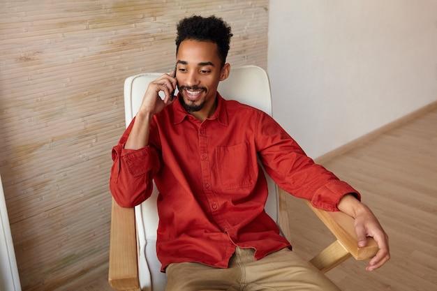 Vrolijke jonge mooie bebaarde brunette man met donkere huid lacht graag terwijl het hebben van een mooi telefoongesprek, zit interieur in vrijetijdskleding