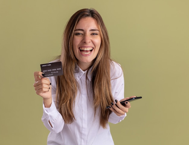 Vrolijke jonge, mooie blanke meid houdt creditcard en telefoon vast