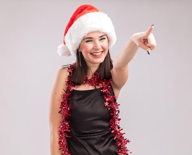 Vrolijke jonge mooie blanke meisje dragen kerstmuts en klatergoud slinger rond nek wijzen en kijken naar kant geïsoleerd op witte achtergrond