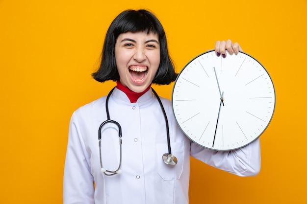 Vrolijke jonge mooie blanke vrouw in doktersuniform met stethoscoop die klok vasthoudt