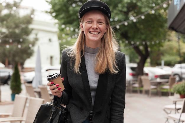 Vrolijke jonge mooie blonde vrouw met afhaalkoffie terwijl ze over de stad loopt voor de werkdag, in een hoge geest is en gelukkig lacht