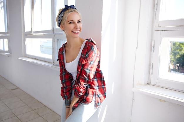 Vrolijke jonge mooie blonde vrouw met casual kapsel achterover leunend op de muur terwijl ze graag naar de voorkant kijkt met een brede glimlach, in een leuke bui terwijl poseren in lichte studio