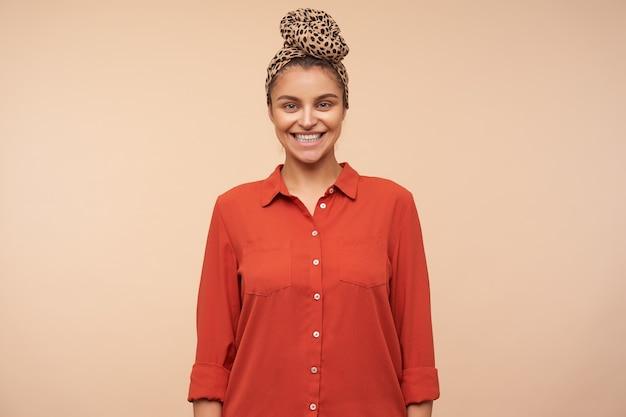 Vrolijke jonge mooie bruinharige vrouw gekleed in trendy kleding kijkt vrolijk naar voren met een brede glimlach, staande over beige muur met handen naar beneden