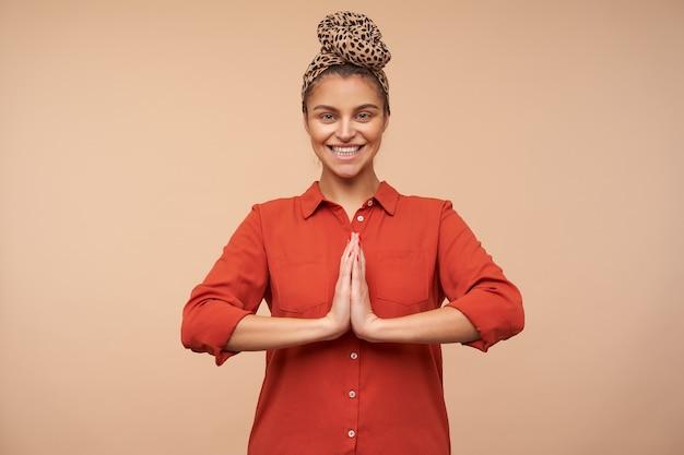 Vrolijke jonge mooie bruinharige vrouw met hoofdband die gelukkig naar voren kijkt met een brede glimlach en opgeheven handpalmen samen vouwen, geïsoleerd over beige muur