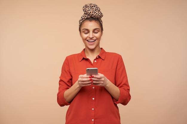 Vrolijke jonge mooie bruinharige vrouw met hoofdband die mobiele telefoon in opgeheven handen houdt en graag naar het scherm kijkt, poseren over beige muur