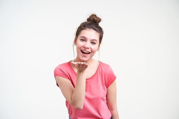 Vrolijke jonge mooie bruinharige vrouw met knot kapsel houden opgeheven hand voor haar gezicht en vrolijk kijken naar camera, geïsoleerd op witte achtergrond