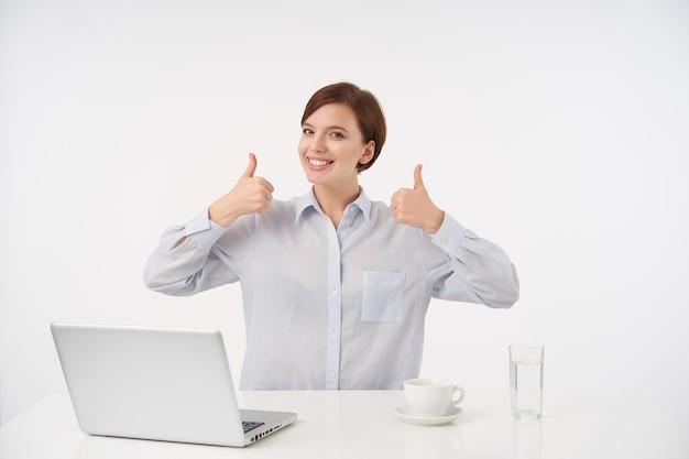 Vrolijke jonge mooie bruinharige vrouw met natuurlijke make-up die gelukkig kijkt en opgeheven duimen toont, formele kleding draagt terwijl poseren op wit