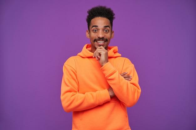 Vrolijke jonge mooie bruinogige donkerhuidige brunette man met baard met opgeheven hand op zijn kin en gelukkig lachend, geïsoleerd op paars in oranje hoodie