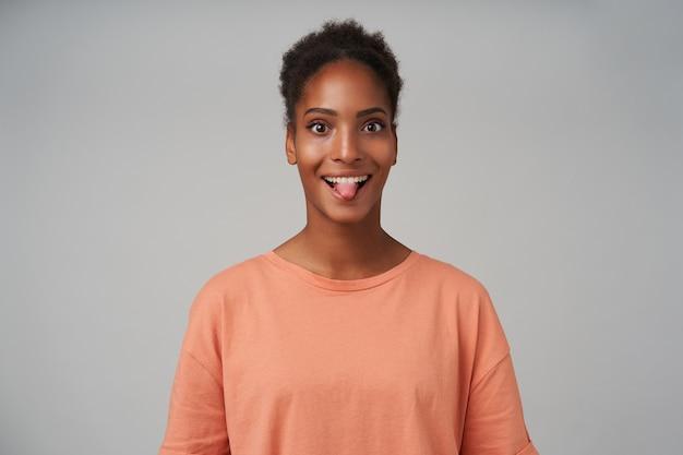 Vrolijke jonge mooie bruinogige krullende brunette vrouw toont haar tong terwijl ze vrolijk kijkt, staande op grijs in roze t-shirt