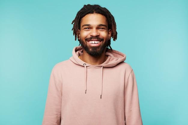 Vrolijke jonge mooie brunette bebaarde man met donkere huid glimlachend wijd terwijl hij gelukkig naar de camera kijkt, handen naar beneden houden terwijl poseren op blauwe achtergrond