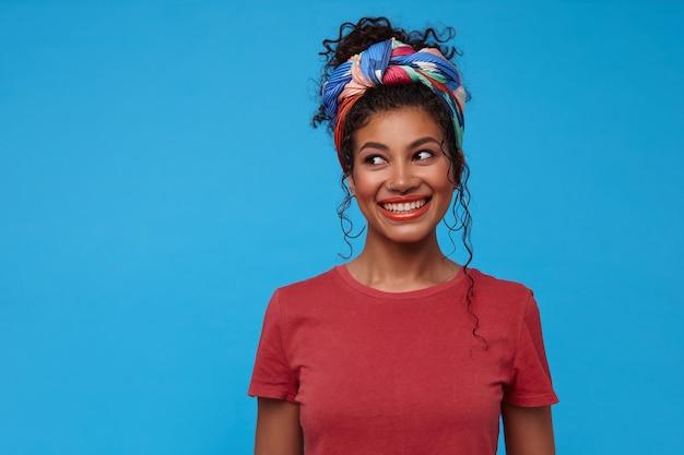 Vrolijke jonge mooie brunette krullende vrouw met verzameld haar die gelukkig opzij kijkt met een brede glimlach, in een hoge geest terwijl ze over de blauwe muur staat