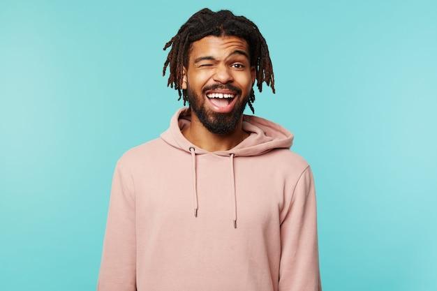 Vrolijke jonge mooie brunette man met donkere huid vrolijk knipogen naar de camera en vrolijk glimlachen, handen naar beneden houden terwijl staande op blauwe achtergrond