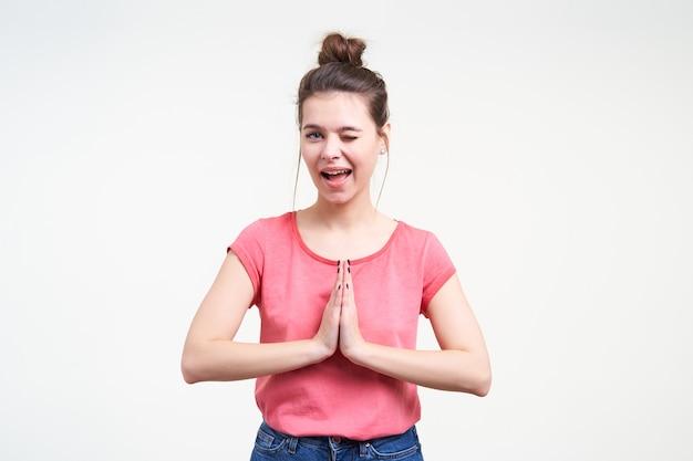 Vrolijke jonge mooie brunette vrouw één oog gesloten houden terwijl ze speels naar de camera kijkt en opgeheven hand vouwen in biddend gebaar, geïsoleerd op witte achtergrond