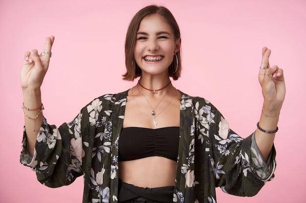 Vrolijke jonge mooie brunette vrouw met bob kapsel glimlachend vreugdevol terwijl ze de handen opheft met gekruiste vingers, staande over roze muur in trendy slijtage