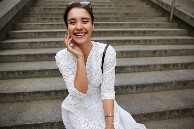 Vrolijke jonge mooie brunette vrouw met zonnebril op haar hoofd gelukkig lachen, in hoge geest zijn en haar gezicht aanraken met opgeheven hand
