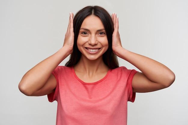 Vrolijke jonge mooie donkerharige dame met natuurlijke make-up haar oren sluiten met handen en gelukkig kijken en breed glimlachen, staande Gratis Foto