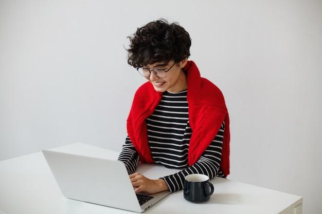 Vrolijke jonge mooie donkerharige gekrulde vrouw in brillen handen houden op toetsenbord terwijl positief kijken naar scherm met brede glimlach, poseren