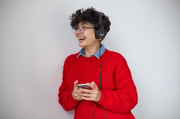 Vrolijke jonge mooie donkerharige gekrulde vrouw met korte trendy kapsel mobiele telefoon in opgeheven handen houden en gelukkig lachen terwijl opzij kijken, poseren op witte achtergrond met koptelefoon