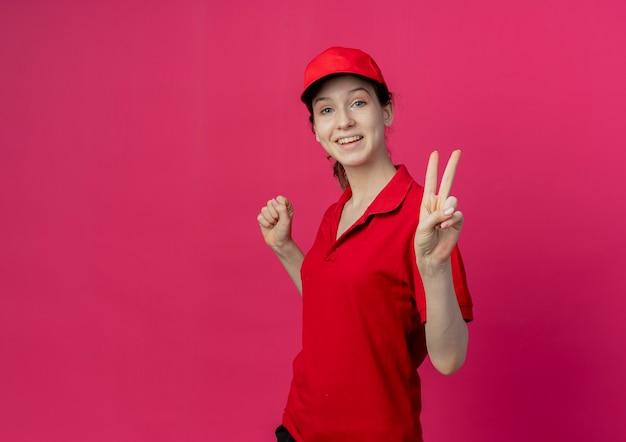 Vrolijke jonge mooie levering meisje in rood uniform en pet staande in profiel te bekijken gebalde vuist en vredesteken geïsoleerd op karmozijnrode achtergrond met kopie ruimte doen