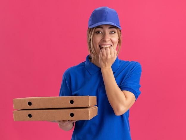 Vrolijke jonge mooie levering meisje in uniform bijt vingers en houdt pizzadozen op roze