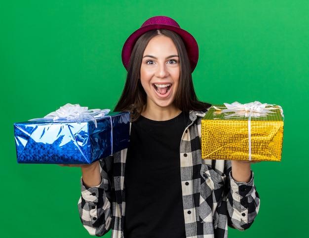 Vrolijke jonge, mooie meid met een feesthoed die geschenkdozen op de camera vasthoudt