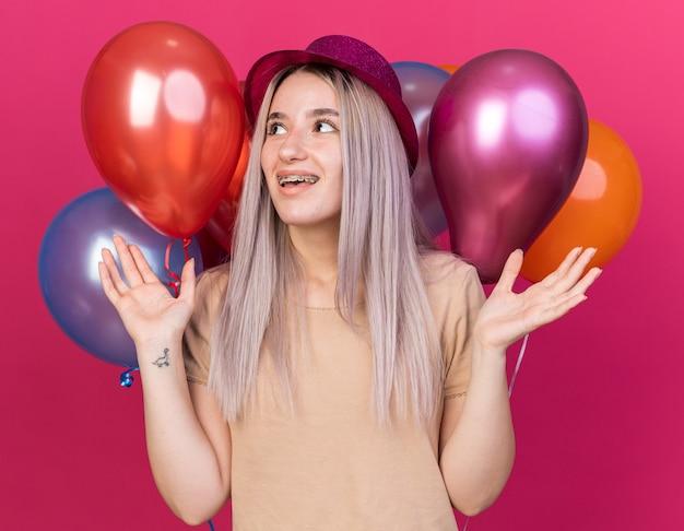 Vrolijke jonge, mooie meid met een feesthoed die vooraan staat met ballonnen die handen uitspreiden die op roze muur zijn geïsoleerd