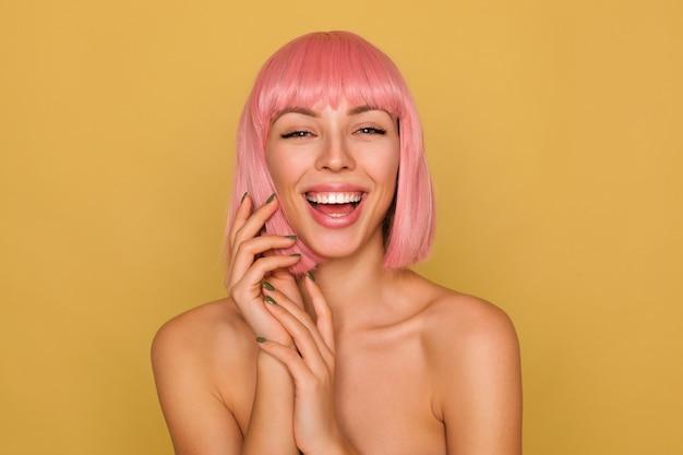 Vrolijke jonge mooie roze harige vrouw die gelukkig lacht terwijl ze kijkt en opgeheven handen vouwt terwijl ze poseren over mosterdmuur