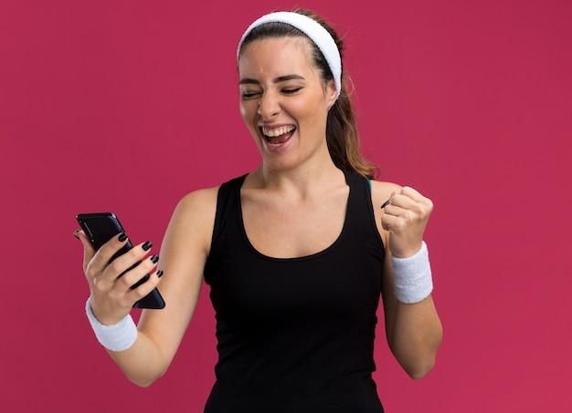 Vrolijke jonge, mooie sportieve meid met een hoofdband en polsbandjes die een mobiele telefoon vasthoudt en kijkt en ja gebaar doet