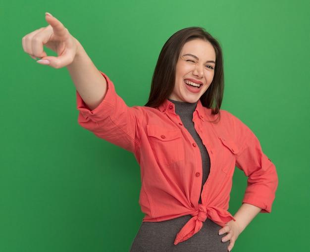 Vrolijke jonge mooie vrouw die de hand op de taille houdt en recht naar de zijkant wijst die op een groene muur knipoogt