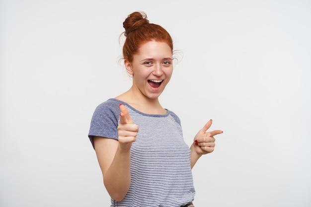 Vrolijke jonge mooie vrouw die haar foxyhaar in de knoop draagt terwijl ze over een witte muur poseert, haar wijsvingers omhoog houdt en graag kijkt