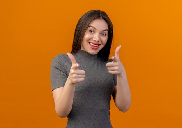 Vrolijke jonge mooie vrouw die je gebaar doet bij camera die op oranje achtergrond met exemplaarruimte wordt geïsoleerd