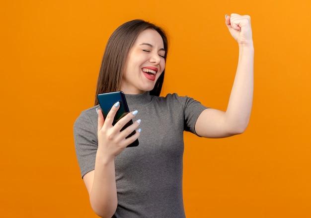 Vrolijke jonge mooie vrouw die mobiele telefoon houdt die vuist opheft die ja gebaar met gesloten ogen doet