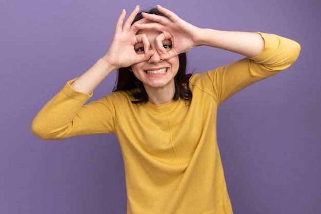 Vrolijke jonge mooie vrouw die naar de voorkant kijkt en een gebaar doet met handen als verrekijker geïsoleerd op een paarse muur