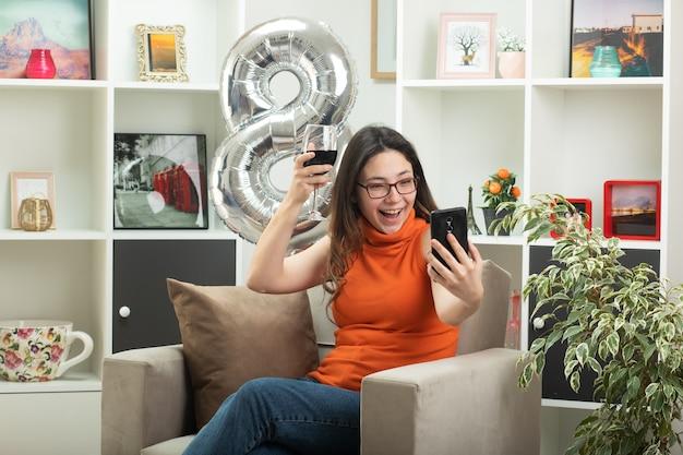 Vrolijke jonge mooie vrouw in glazen met glas wijn en kijken naar telefoon zittend op een fauteuil in de woonkamer op maart internationale vrouwendag
