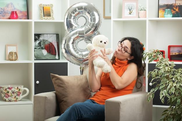 Vrolijke jonge mooie vrouw met een bril die een witte teddybeer vasthoudt en bekijkt die op een leunstoel in de woonkamer zit op de internationale vrouwendag van maart