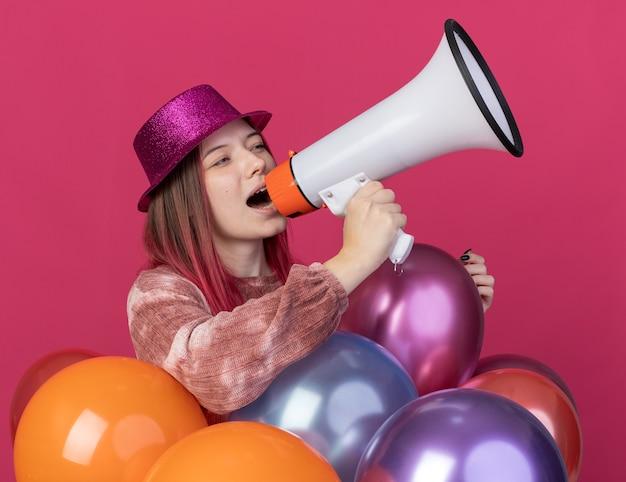 Vrolijke jonge mooie vrouw met feestmuts die achter ballonnen staat, spreekt op luidspreker geïsoleerd op roze muur