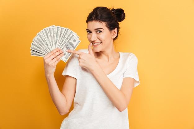 Vrolijke jonge mooie vrouw met geld wijzen.
