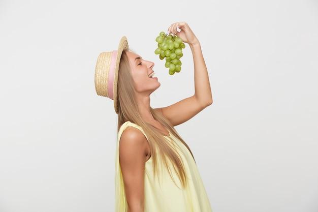 Vrolijke jonge mooie vrouw met lang blond haar groene druiven in opgeheven hand houden en gaan proeven, vrolijk glimlachend terwijl poseren op witte achtergrond