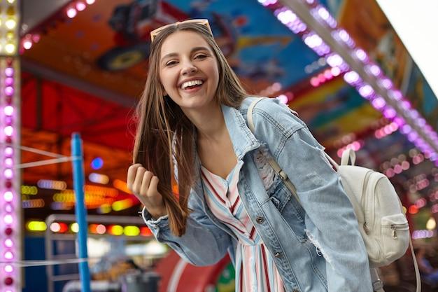 Vrolijke jonge mooie vrouw met lang bruin haar wandelen in het park van attracties, het dragen van vrijetijdskleding en witte rugzak, houdt haar haren vast en kijkt met een brede oprechte glimlach