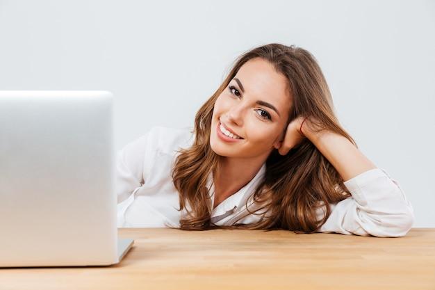 Vrolijke jonge mooie vrouw zit aan de balie met laptop op witte achtergrond