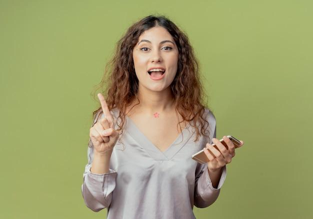 Vrolijke jonge mooie vrouwelijke kantoormedewerker met telefoon en punten aan de zijkant