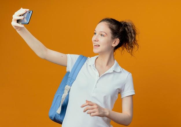 Vrolijke jonge mooie vrouwelijke student die achterzak draagt die selfie houdt hand in lucht
