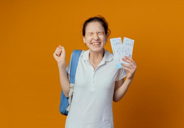 Vrolijke jonge mooie vrouwelijke student die rugtas draagt die vliegtuigtickets houdt die vuist met gesloten ogen balde die op oranje achtergrond met exemplaarruimte wordt geïsoleerd