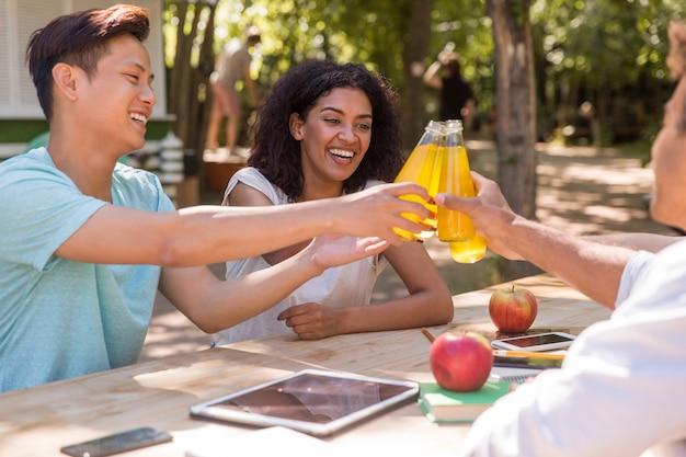 Vrolijke jonge multi-etnische vriendenstudenten die in openlucht juicee drinken.